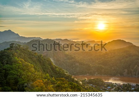 Sunset over lush green jungle covered hills with the Beni River visible in Rurrenabaque, Bolivia - stock photo