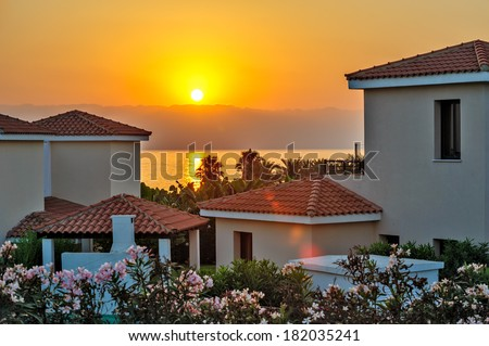 Sunset over luxurious holiday beach villas for rent on Cyprus