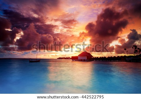 Sunset over Maldives islands, beautiful beach landscape, stunning evening seascape in orange sunset light, summer exotic holidays, travel and tourism concept - stock photo