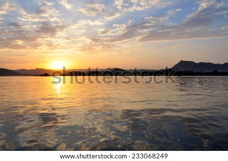 Sunset over man-made lake asseen from the famous Jag Niwas lake palace in Udaipur, Rajasthan, India - stock photo