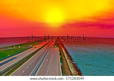 Sunset over Modern Highway on the Protective Dam in Netherlands - stock photo