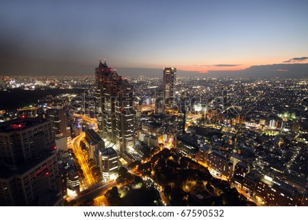 Sunset over modern skyscrapers and illuminated houses over Tokyo, Japan - stock photo