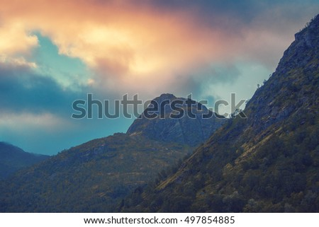 Sunset over mountains. Evening cloudy sky over mountains peaks