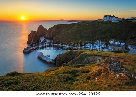 Sunset over Mullion Cove of small harbour on the Lizard peninsula in south Cornwall, United Kingdom. - stock photo
