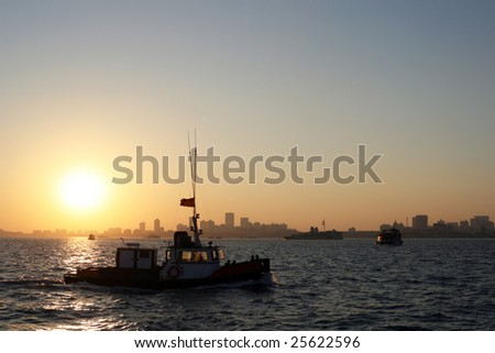 Sunset over Mumbai and a boat crossing the reflection of the sun in the ocean - stock photo