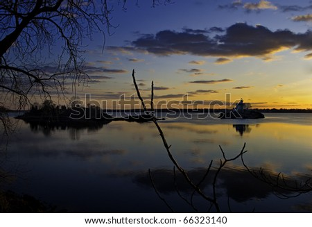 Sunset over Narragansett bay, RI, showing a clear winter evening with a sunset reflected in the water. A lighthouse spices up the horizon line. - stock photo