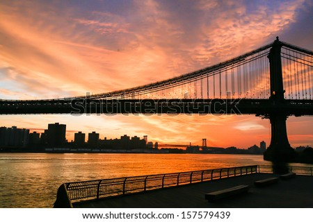 Sunset over New York City, filming on the south side of the Brooklyn Bridge, Brooklyn Bridge in the frame, water surface, embankment.Photos from my month tour of America - stock photo