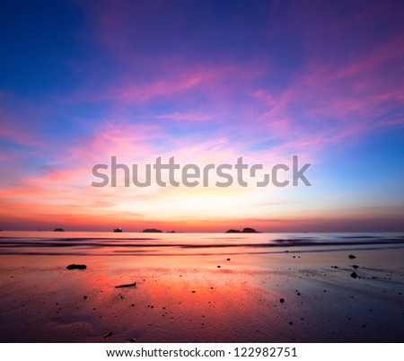 Sunset over ocean at low tide - stock photo