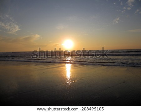 Sunset over ocean waves crashing along the beach on Half Moon Bay in California with sunlight reflecting on the water.                                - stock photo