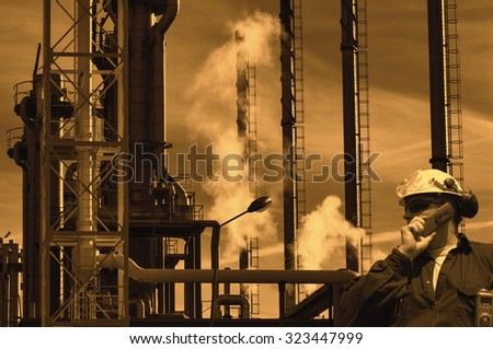 sunset over oil and gas refinery, worker in foreground - stock photo