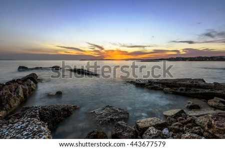 Sunset over old pier in the sea in south Athens, Greece