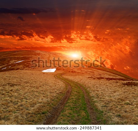 sunset over path in mountains - stock photo
