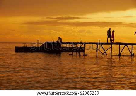 Sunset over pier in town's beach in Montenegro southeast Europe - stock photo