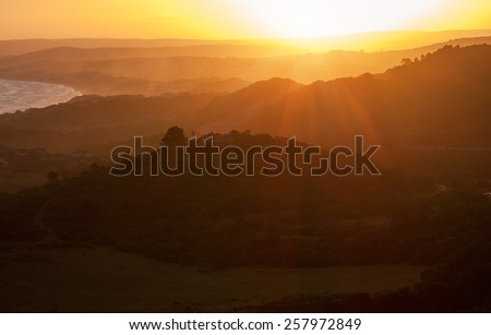sunset over receding hills and mountain with yellow sunny background of rays of sunlight over hills and valleys - stock photo