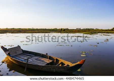 Sunset over rice field lake with a boat in Cambodia