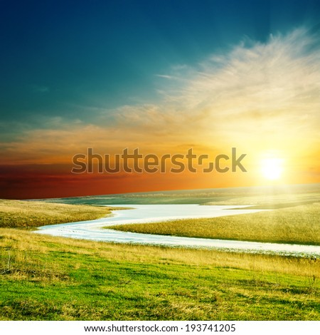 sunset over river in green grass