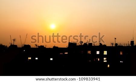 Sunset over rooftops with building lights - stock photo