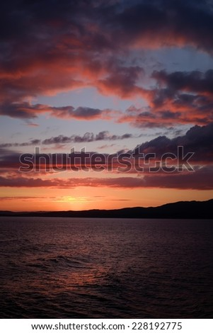Sunset over sea - Sunset view from the ferry from Islay to mainland Scotland - stock photo