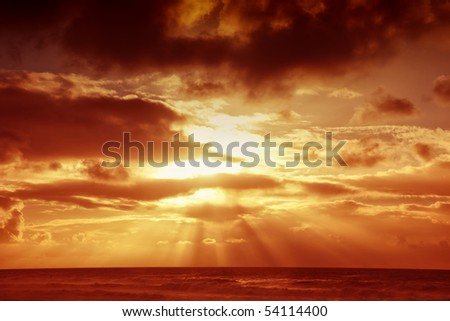 Sunset over sea with moody sky, dark storm clouds, and red light. Makes a good background. - stock photo