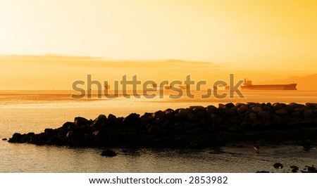 Sunset over ships in Vancouver Harbour - stock photo