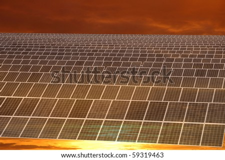 Sunset over solar power station - stock photo