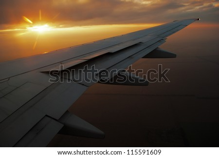 Sunset over the airplane wing - stock photo