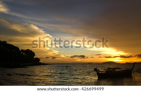 Sunset over the beach with fisherman boat silhouettes.
