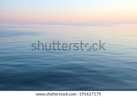 Sunset over the calm ocean. View towards the horizon.  - stock photo