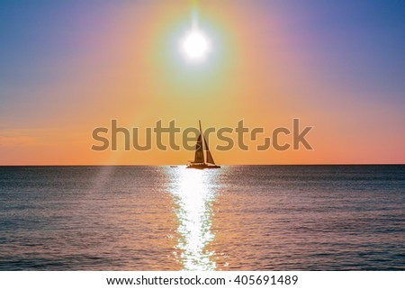 sunset over the caribbean sea with boat on the horizon
