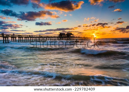 Sunset over the fishing pier and Gulf of Mexico in Naples, Florida.