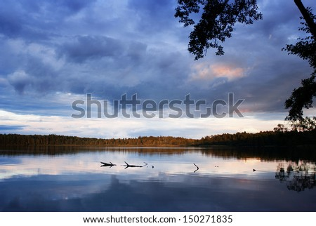 Sunset over the forest lake with dramatic sky. - stock photo