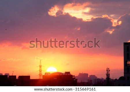 sunset over the gurgaon cityscape with monsoon clouds and the silhouette of buildings
