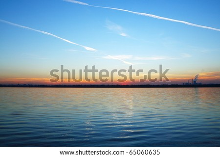 Sunset over the lake and a factory on the horizon - stock photo