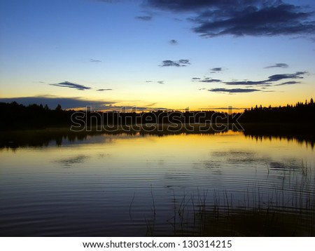 Sunset over the lake and forest. Russia - stock photo