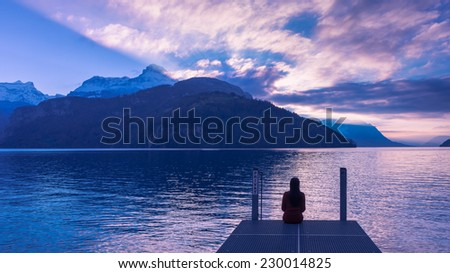 "Sunset over the lake and mountains colored water sky and clouds in pink purple color. Young woman with long hair sitting on the dock with the word ""Private"". - stock photo"