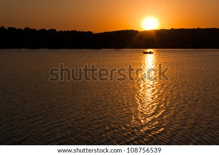 sunset over the lake, boat crossing the lake, landscape image