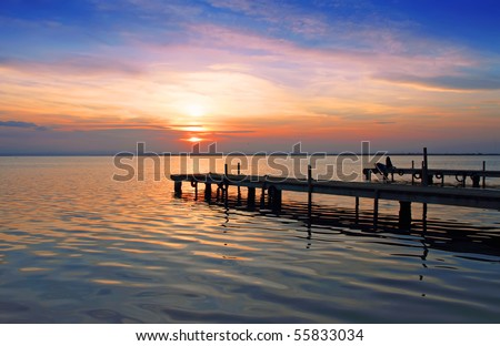 sunset over the lake from piers - stock photo