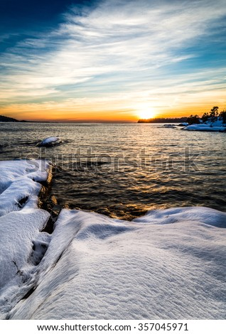 Sunset over the lake, Rocks with snow in the foreground.