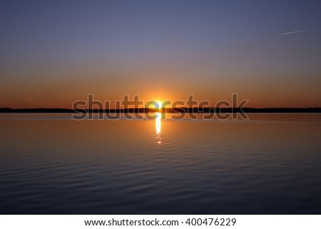 Sunset over the lake with cloudless sky, the trail from an airplane, calm water - stock photo