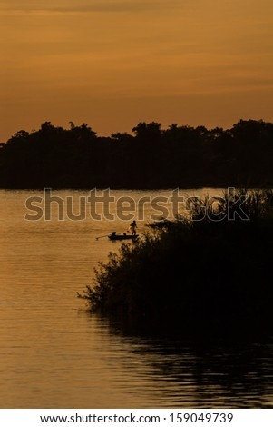 Sunset over the Mekong River near the island of Don Det in the Mekong Delta. Silhouette of a fisherman in his boat who is throwing out is nets in the evening.  - stock photo