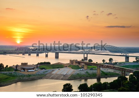 Sunset over the Mississippi River, Hernando de Soto Bridge, and Mud Island River Park in Memphis, Tennessee, USA. - stock photo
