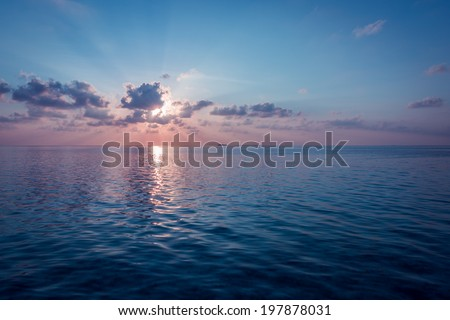 Sunset over the Ocean. Rays of the sun through the clouds. Setting sun painted the sky and ocean in deeply bright   color. - stock photo