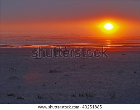 Sunset over the ocean with a beach foreground - stock photo