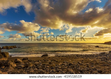Sunset over the ocean with amazing clouds in the sky. - stock photo