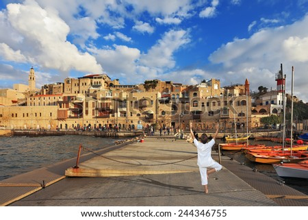 "Sunset over the Old Jaffa in Tel Aviv. Fishing jetty port,  the woman in white performs asana ""Tree"" on one leg - stock photo"