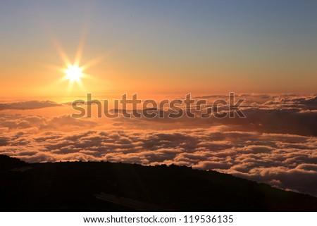 Sunset over the Pacific Ocean from Mount Haleakala on Maui, Hawaii - stock photo
