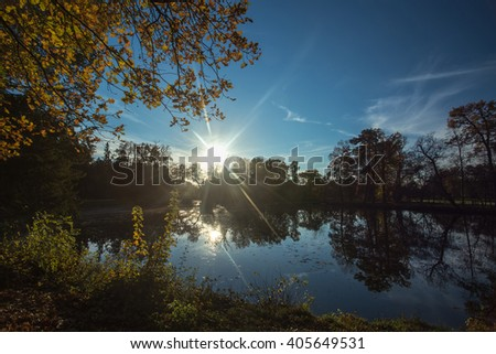 Sunset over the pond. Trees are reflected in the lake. Autumn color landscape - stock photo