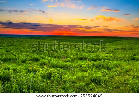 Sunset over the prairie land that is so important to the ranchers in the Flint Hills of Kansas.  Kansas is also known to be one of the top 10 places in the world for sunsets. - stock photo