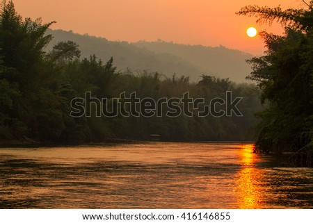 Sunset over the River Kwai Kanchanaburi Thailand. View from the boat, image in the orange toning.Toned image - stock photo