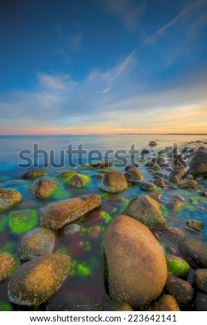 Sunset over the rolling stones of the Norwegian coast, Moelen - stock photo